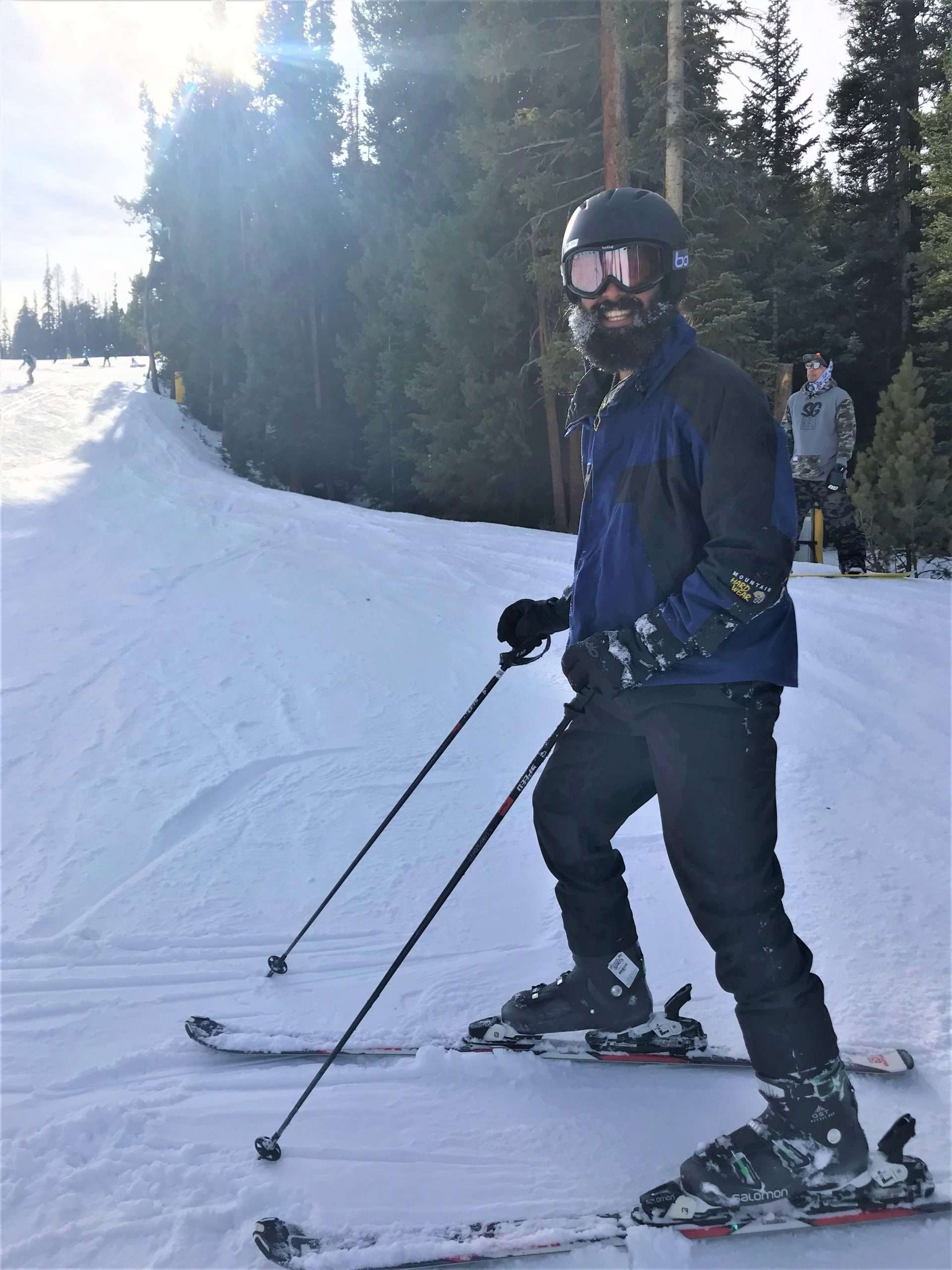 Skier stopped on blue run and smiling at camera