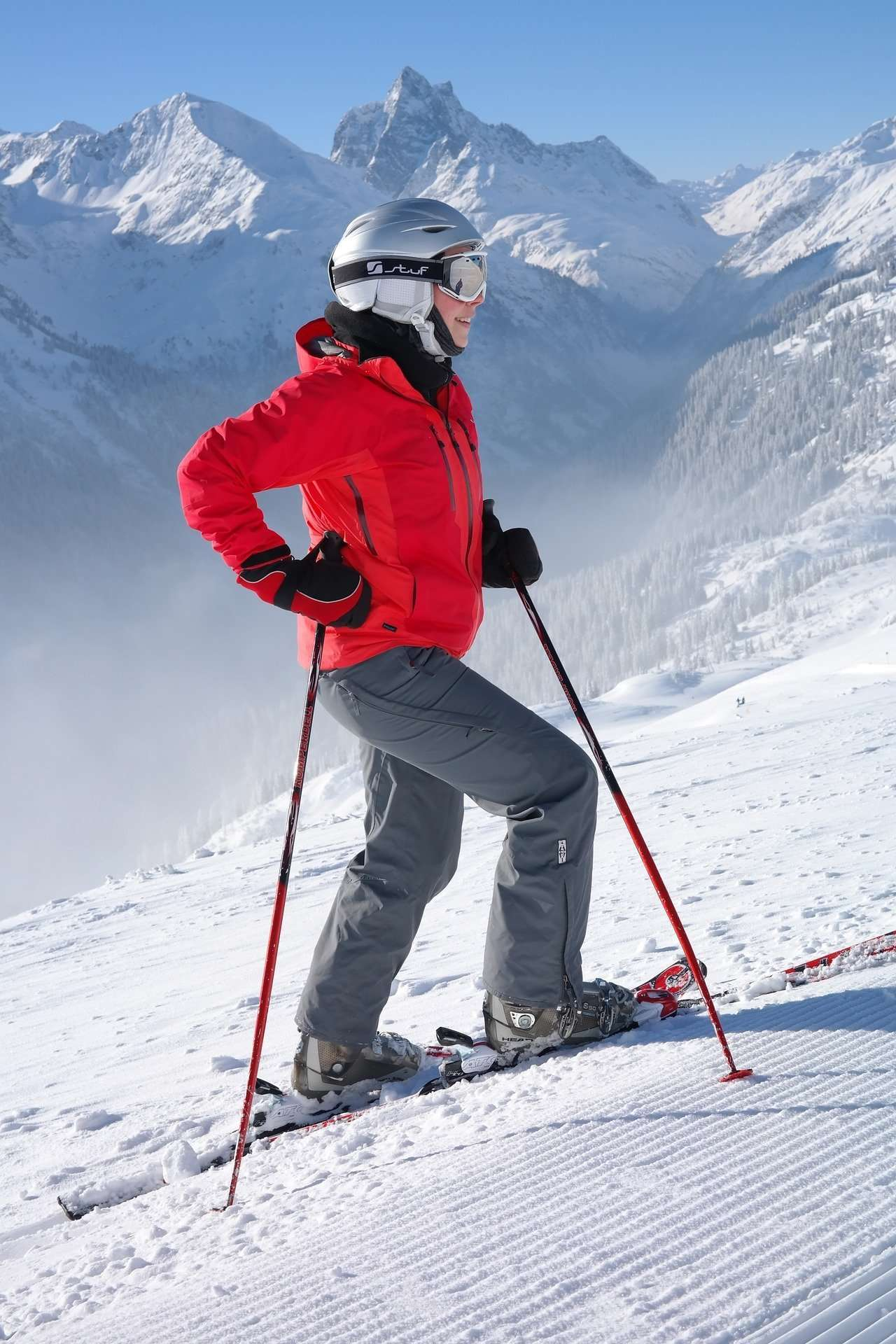 Skier in red jacket posing with ski poles
