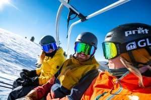 Three skiers on chairlift with ski goggles on
