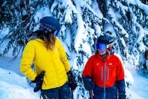 Two skiers in vibrant ski jackets