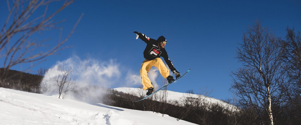 Snowboarder in black hoodie and yellow pants doing a trick in the air