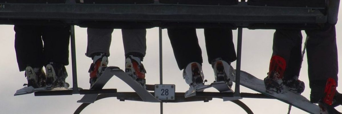 Three skiers and snowboarder resting feet on chairlift