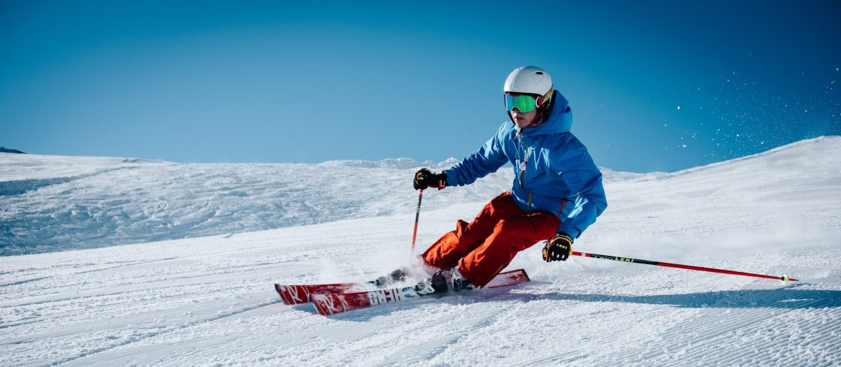 Skier in blue jacket and red pants intensely carving down slope