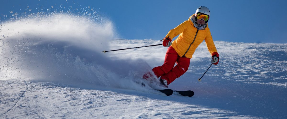 Skier in yellow jacket and red pants skiing downhill