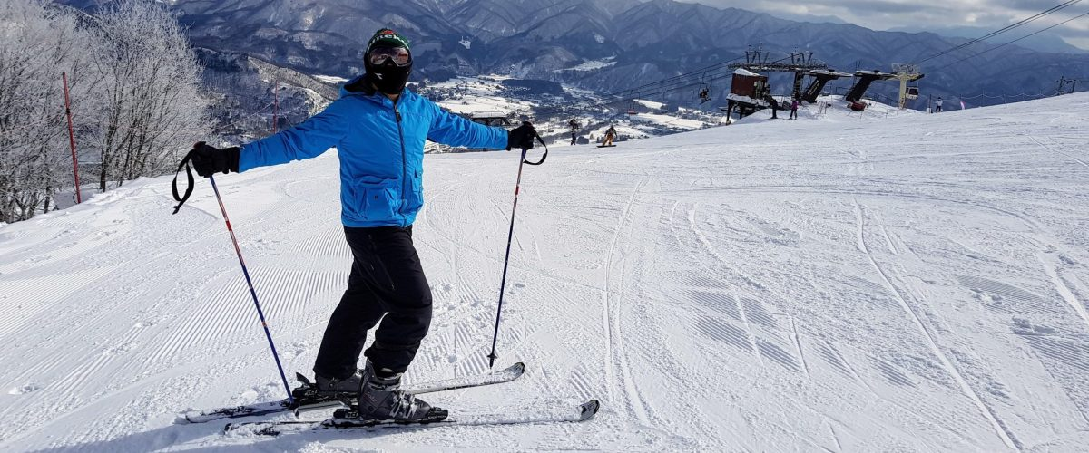 Skier in blue jacket and black pants standing sideways on hill with arms out