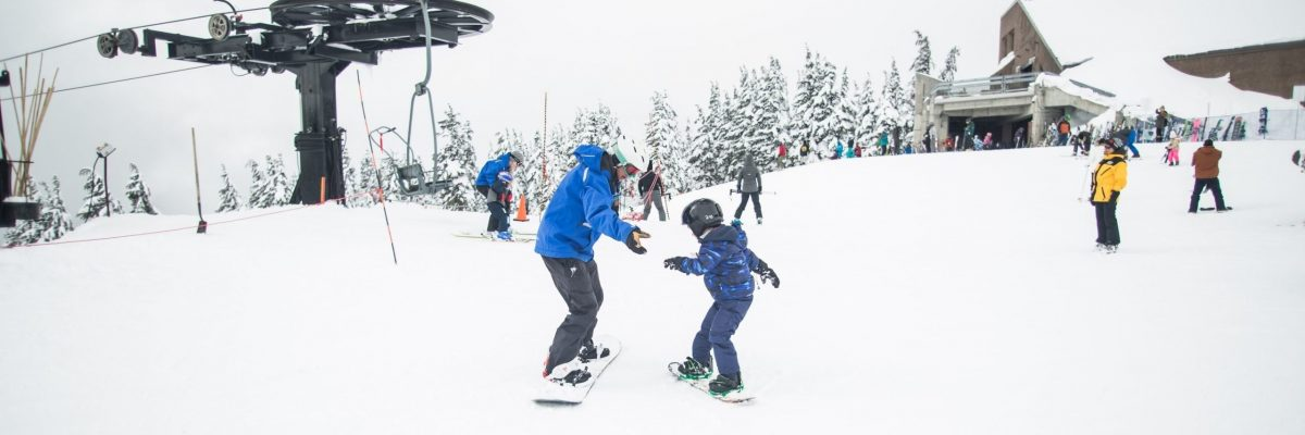 Adult helping child glide on snowboard