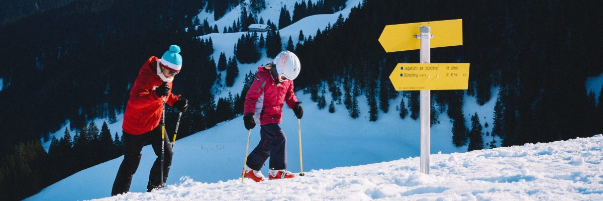 Woman and child walking uphill on skis