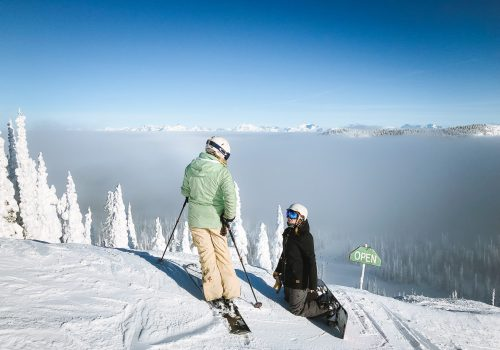 Skier and snowboarder at top of slope