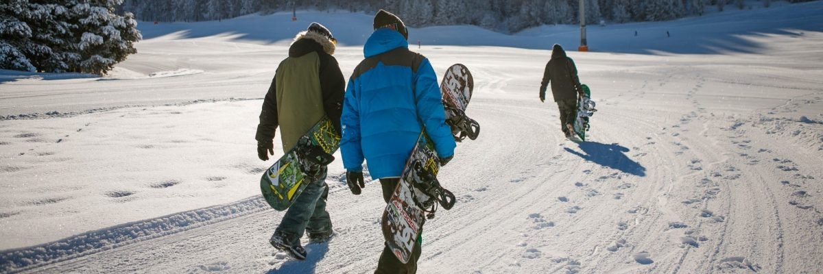 Three snowboarders walking and carrying their boards