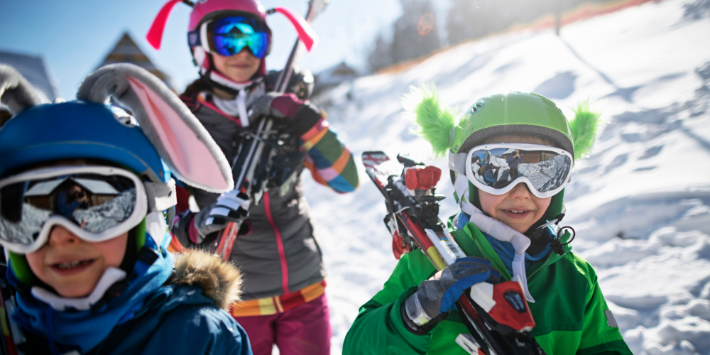 Group of kids carrying skis