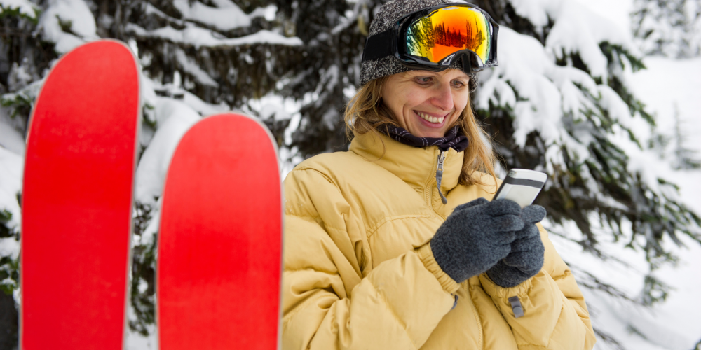 Woman wearing ski glove liners while texting