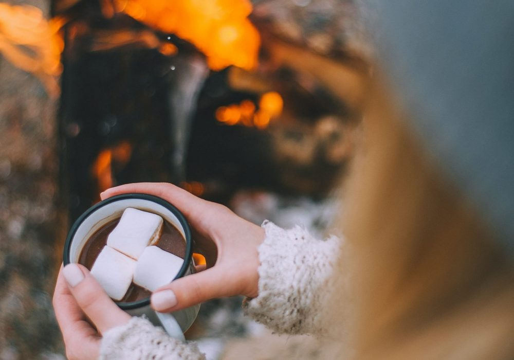 Keeping hands warm by fire with hot chocolate