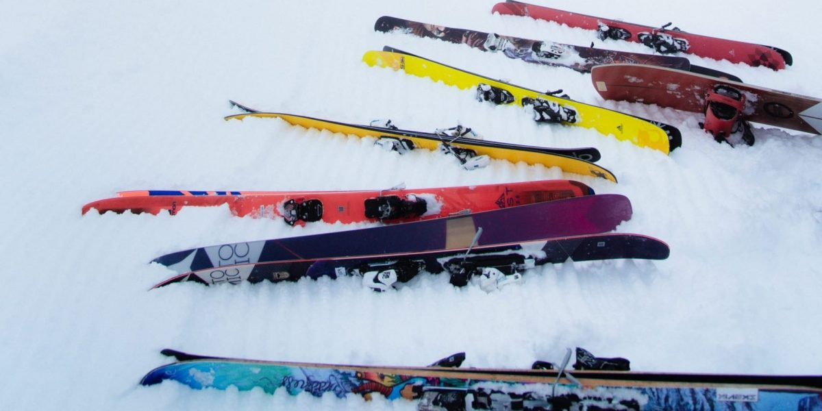 Several pairs of skis laying on the ground