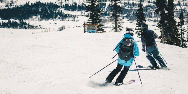 Two people skiing toward a black diamond run