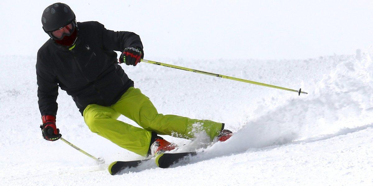 Skier carving down black diamond