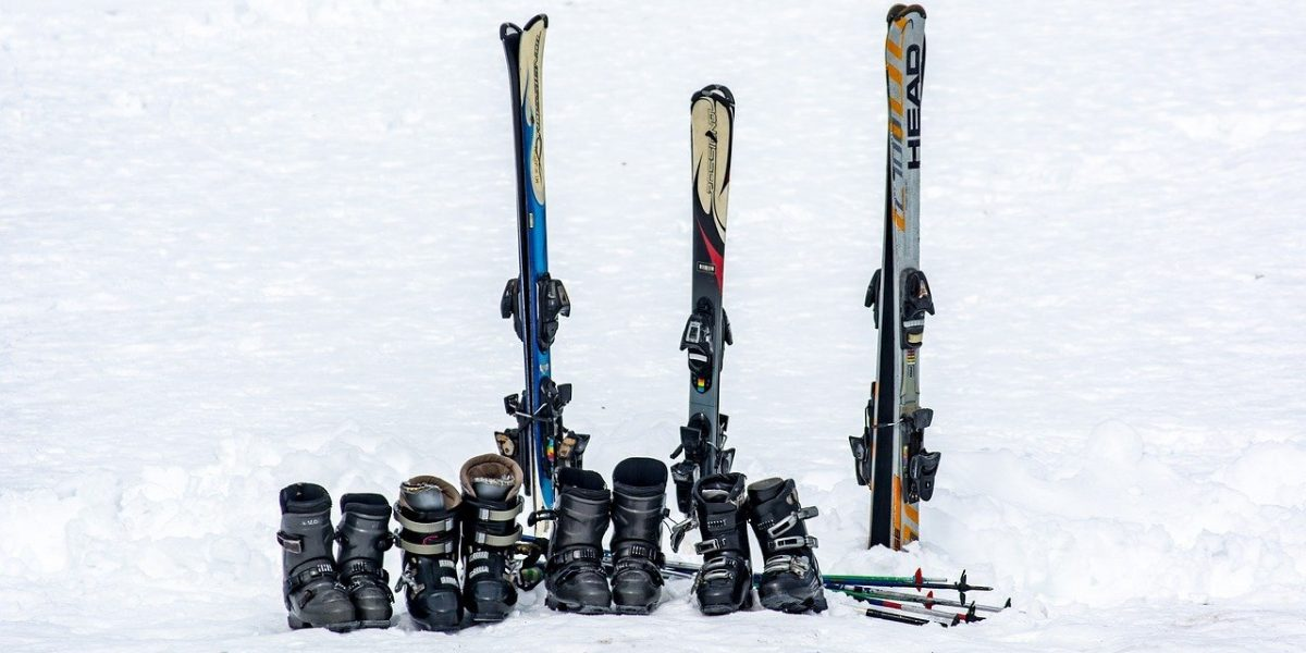 Three pairs of skis and boots in snow