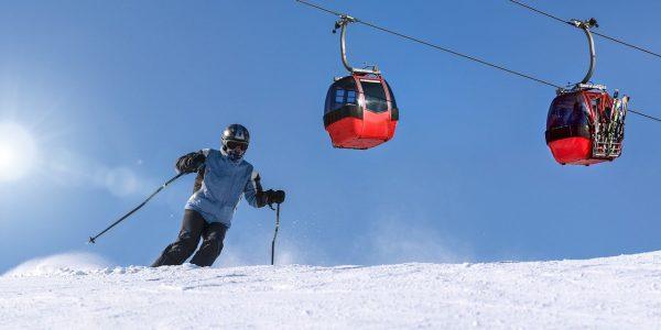 Skier skiing below gondola