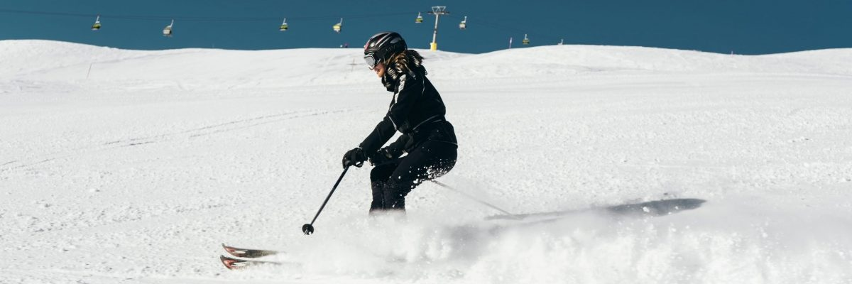 Woman skiing across slope with knees bent